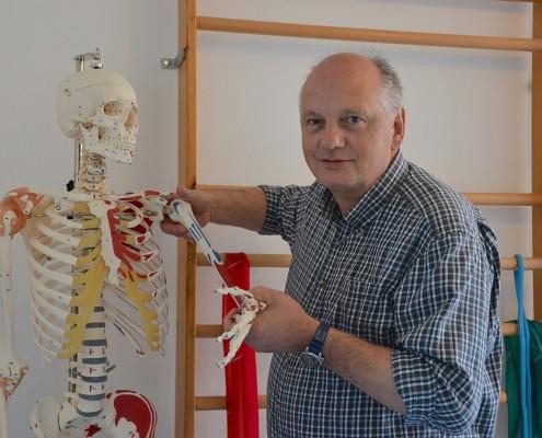 Herr Detlef Miebs steht neben einem farblich markierten Skelett und hebt den linken Arm hervor