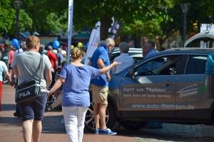 Menschen bei der Tibarg Autoschau 2016 in Hamburg-Niendorf in einem Gespräch vor einem Ausstellungswagen