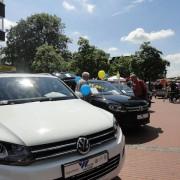 Das Foto zeigt ein weißes und schwarzes VW-Modell sowie interessierte Besucher.