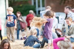 Kinder beim Spielen mit Heu auf dem Tibarg Bauernmarkt