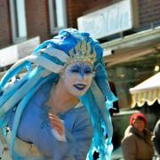 Eine Künstlerin in fantasievoller, blauer Kleidung und Kopfschmuck unterhält die Besucher.