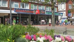 Sicht auf die Heudorfer Apotheke mit blühendem Blumenbeet im Vordergrund