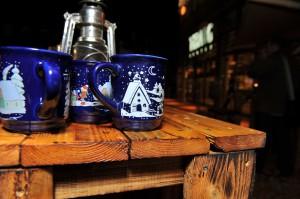 Drei blaue Glühweinbecher mit weihnachtlichen Motiven auf einem alten Holztisch.