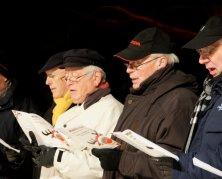 Das Bild zeigt vier Männer die gemeinsam Singen und dabei die Noten aus ihren Liederheften ablesen.