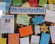 Das Bild zeigt verschiedene, bunte Wunschzettel an einer Fensterscheibe.