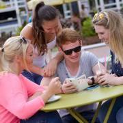 Ein Gruppe von vier Freunden sitzt an einem Café-Tisch und schaut gemeinsam auf ein Smartphone.