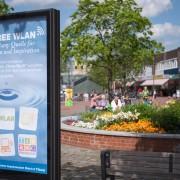 Das Foto zeigt eine Werbetafel auf dem Dorfplatz am Tibarg in Hamburg-Niendorf vor einem hübschen Blumenbeet